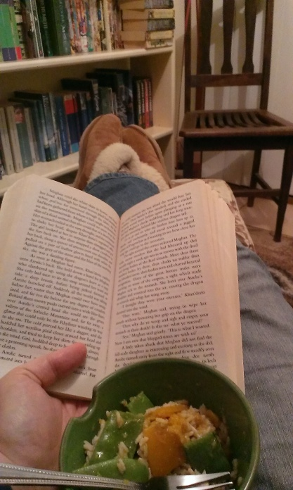 A book and a bowl of food on my lap while I am reclining for dinner and a read, with my feet in ugg boots in the background.